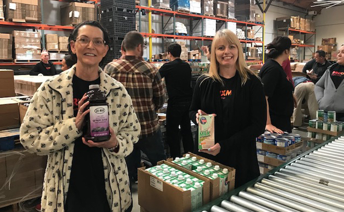 Two Brixmor volunteers on a packing line at food bank