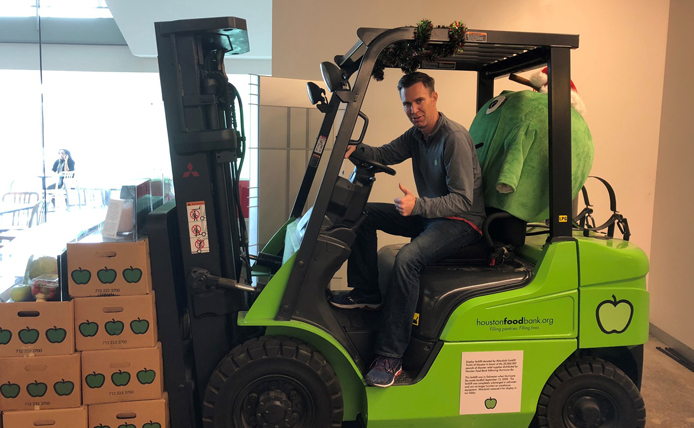 person at Houston Food Bank sitting in a forklift carrying boxes