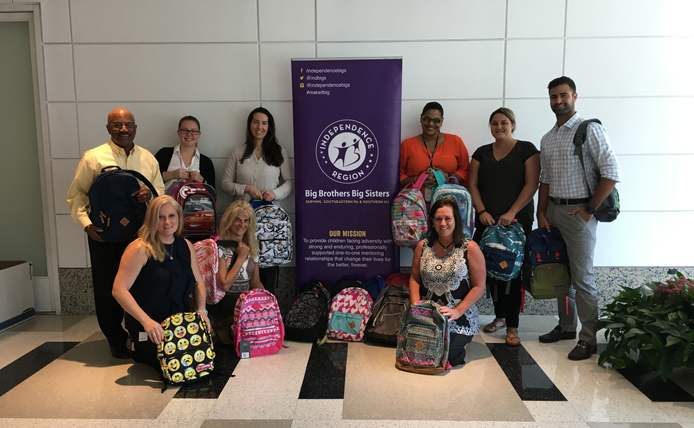 Brixmor employees at Big Brother Big Sister holding backpacks